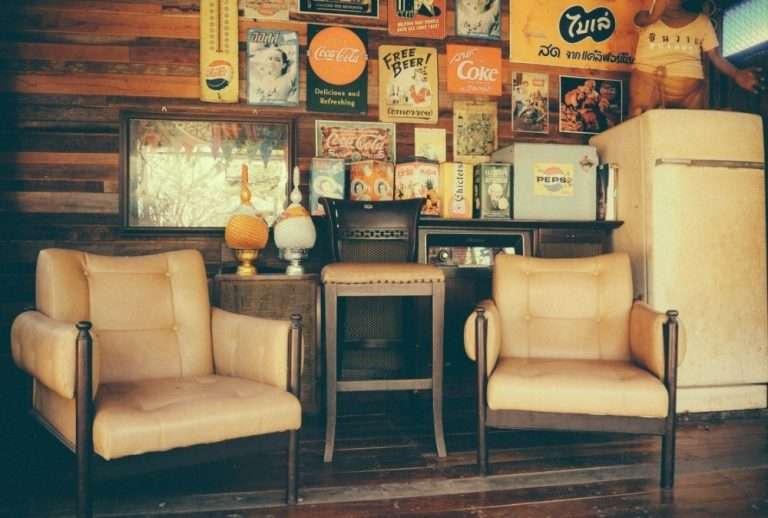 Living vintage con pared decorada con carteles metálicos antiguos